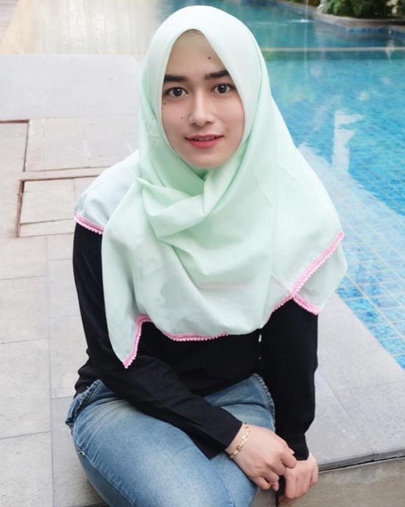 Cewek hijab manis kumis tipis duduk dipinggir kolam renang