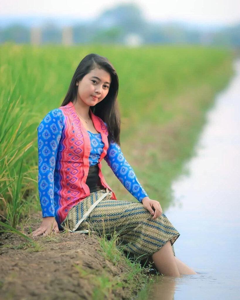 Cewek manis pakai sarung batik manis duduk di pinggir sungai dan sawah desa manis